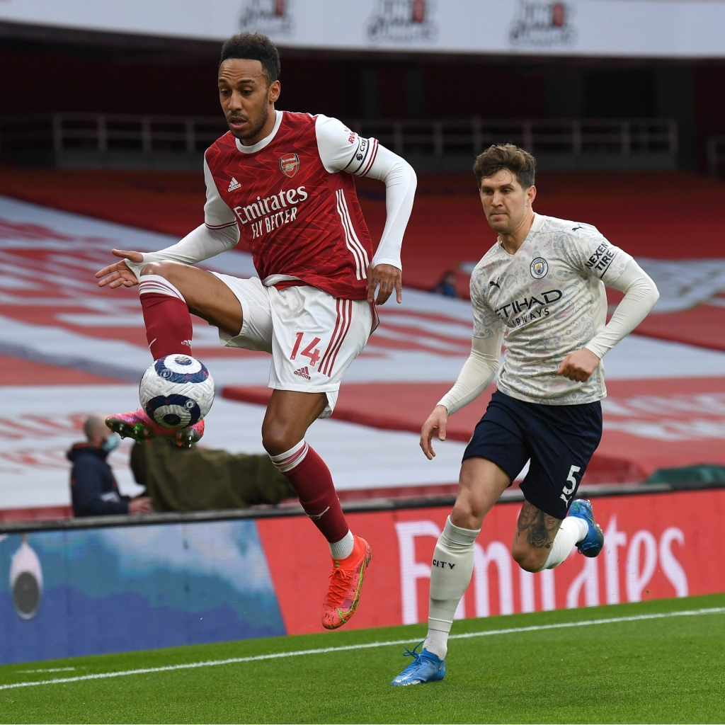 LONDON, ENGLAND - FEBRUARY 21: Pierre-Emerick Aubameyang of Arsenal controls the ball as John Stones of Man City closes in during the Premier League match between Arsenal and Manchester City at Emirates Stadium on February 21, 2021 in London, England. Sporting stadiums around the UK remain under strict restrictions due to the Coronavirus Pandemic as Government social distancing laws prohibit fans inside venues resulting in games being played behind closed doors. (Photo by David Price/Arsenal FC via Getty Images)